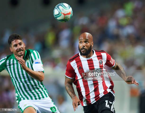 Javi Garcia of Real Betis Balompie duels for the ball with David McGoldrick of Sheffield United during a preseason friendly match between Real Betis...