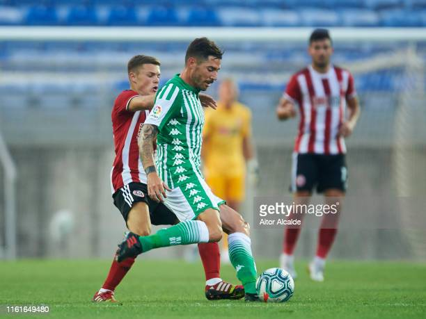 Javi Garcia of Real Betis Balompie duels for the ball with Regan Slater of Sheffield United during a preseason friendly match between Real Betis...