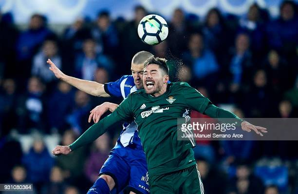 Javi Garcia of Real Betis Balompie duels for the ball with Victor Laguardia of Deportivo Alaves during the La Liga match between Deportivo Alaves and...