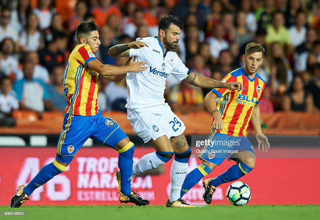 Javi Jimenez (L) and Alvaro Medran (R) of Valencia competes for the ball with Andrea Petagna of Atalanta during the pre-season friendly match between Valencia CF and Atalanta BC at Estadio Mestalla on August 11, 2017 in Valencia, Spain.