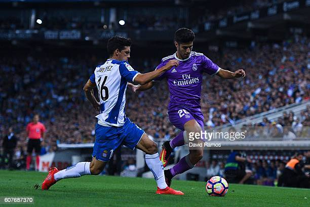 Javi Lopez of RCD Espanyol competes for the ball with Marco Asensio of Real Madrid CF during the La Liga match between RCD Espanyol and Real Madrid...