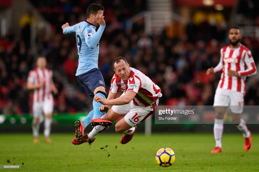 Javi Manquillo of Newcastle United collide with Charlie Adam of Stoke City during the Premier League match between Stoke City and Newcastle United at Bet365 Stadium on January 1, 2018 in Stoke on Trent, England.
