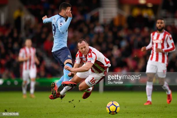 Javi Manquillo of Newcastle United collide with Charlie Adam of Stoke City during the Premier League match between Stoke City and Newcastle United at...