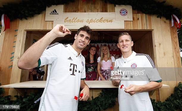 Javi Martinez and Bastian Schweinsteiger of FC Bayern Muenchen present their new trikot in bavarian style while playing Oktoberfest games at Saebener...