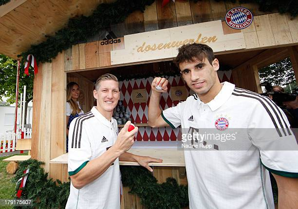 Javi Martinez and Bastian Schweinsteiger of FC Bayern Muenchen present their new trikot in bavarian style while playing Oktoberfest games at Saebener...