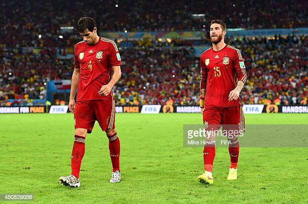 Javi Martinez and Sergio Ramos of Spain walk off the pitch after the 2014 FIFA World Cup Brazil Group B match between Spain and Chile at Estadio...