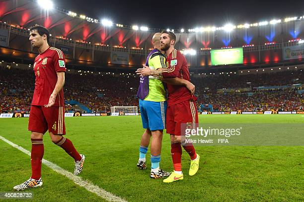 Javi Martinez and Sergio Ramos of Spain walk off the pitch while teammate Pepe Reina consoles after the 2014 FIFA World Cup Brazil Group B match...