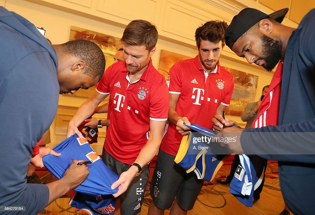 Javi Martinez (2ndR) and Xabi Alonso (2ndL) of Bayern Muenchen rget their basketball jerseys signed by NBA players DeMarcus Cousins (R) of Sacramento Kings and Harrison Barnes of Dallas Mavericks during a training session during the AUDI Summer Tour USA 2016 on July 28, 2016 in Chicago, Illinois.