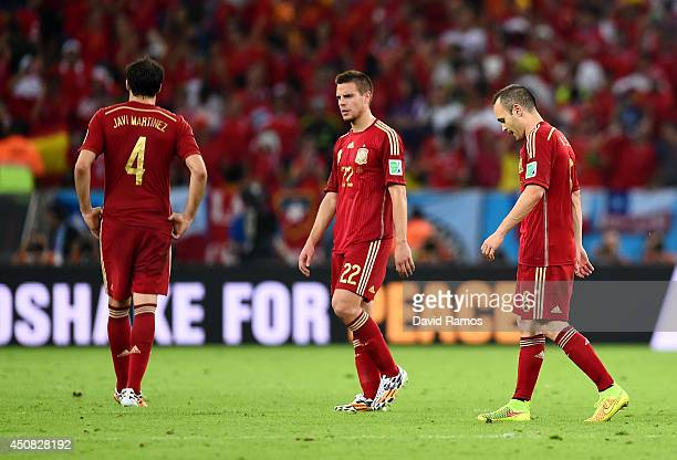 Javi Martinez Cesar Azpilicueta and Andres Iniesta of Spain look dejected after a 20 defeat to Chile in the 2014 FIFA World Cup Brazil Group B match...