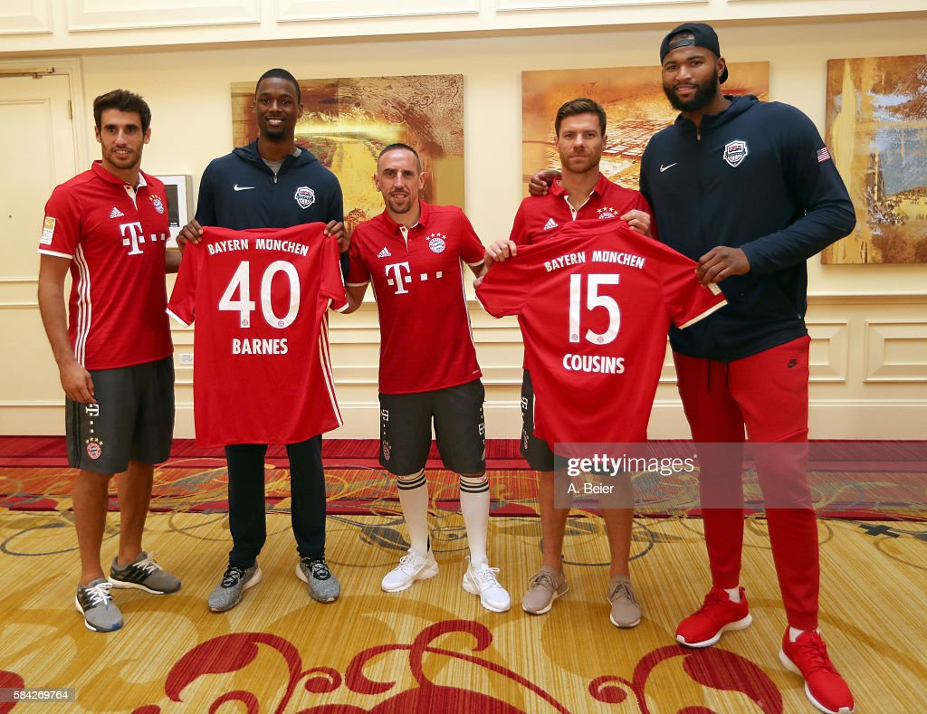 Javi Martinez (L), Franck Ribery (C) and Xabi Alonso (2ndR) of Bayern Muenchen pose with NBA players DeMarcus Cousins (R) of Sacramento Kings and Harrison Barnes of Dallas Mavericks holding FC Bayern Muenchen soccer jerseys during an activity session during the AUDI Summer Tour USA 2016 on July 28, 2016 in Chicago, Illinois.