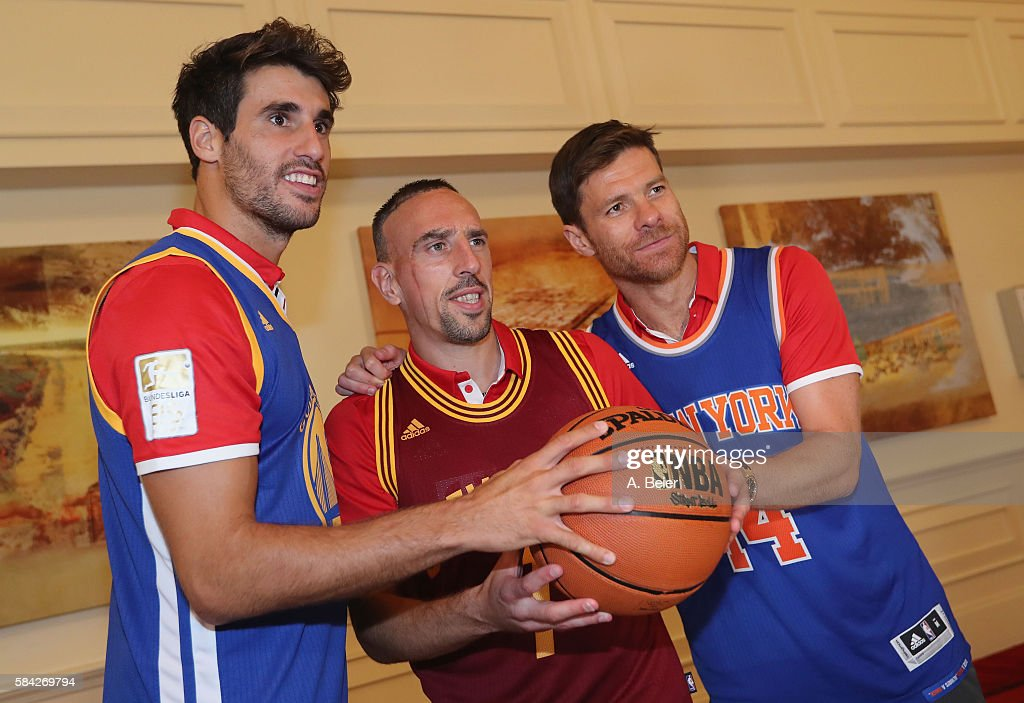 Javi Martinez, Franck Ribery and Xabi Alonso (L-R) of Bayern Muenchen with NBA basketball shirts during an activity session with players DeMarcus Cousins of Sacramento Kings and Harrison Barnes of Dallas Mavericks during the AUDI Summer Tour USA 2016 on July 28, 2016 in Chicago, Illinois.