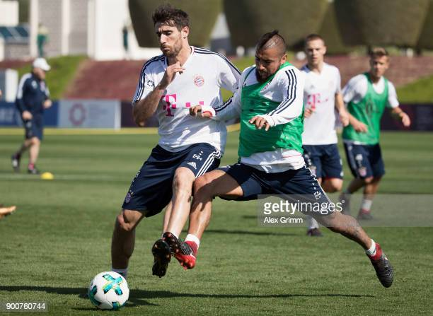 Javi Martinez is challenged by Arturo Vidal during a training session on day 2 of the FC Bayern Muenchen training camp at ASPIRE Academy for Sports...