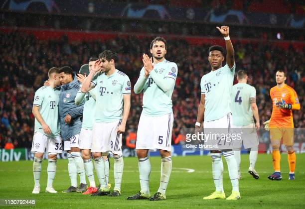 Javi Martinez Mats Hummels and David Alaba of Bayern Munich salute the travelling fans after the UEFA Champions League Round of 16 First Leg match...