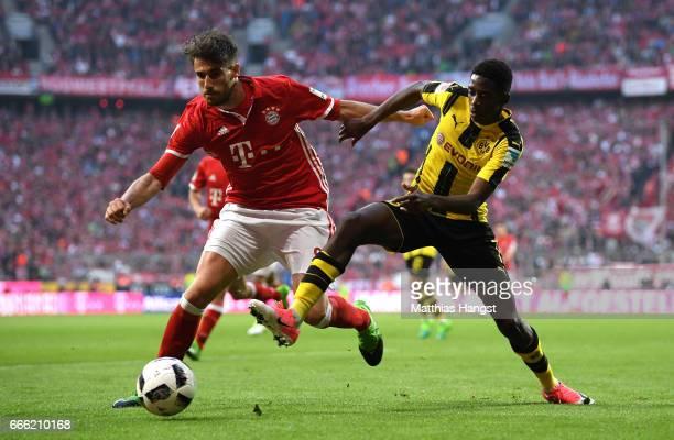Javi Martinez of Bayern Muenchen and Ousmane Dembele of Borussia Dortmund battle for possession during the Bundesliga match between Bayern Muenchen...