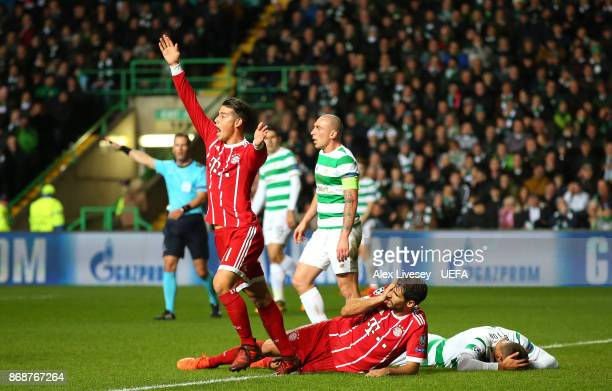 Javi Martinez of Bayern Muenchen lies on the floor after scoring the winning goal but clashing heads with Nir Bitton of Celtic FC as James Rodriguez...