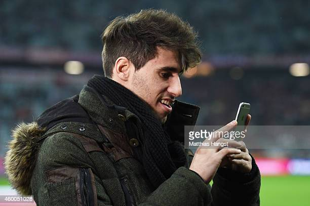 Javi Martinez of Bayern Muenchen takes a photo with his iphone prior to kickoff during the Bundesliga match between FC Bayern Muenchen and Bayer 04...