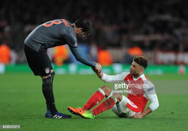 Javi Martinez of Bayern Munich helps up Alex OxladeChamberlain of Arsenal after the UEFA Champions League Round of 16 second leg match between...