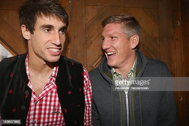 Javi Martinez of FC Bayern Muenchen attends with his team mate Bastian Schweinsteiger the Oktoberfest beer festival at the Kaefer Wiesnschaenke tent...