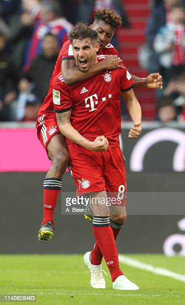 Javi Martinez of FC Bayern Muenchen celebrates his first goal with teammate Kingsley Coman during the Bundesliga match between FC Bayern Muenchen and...