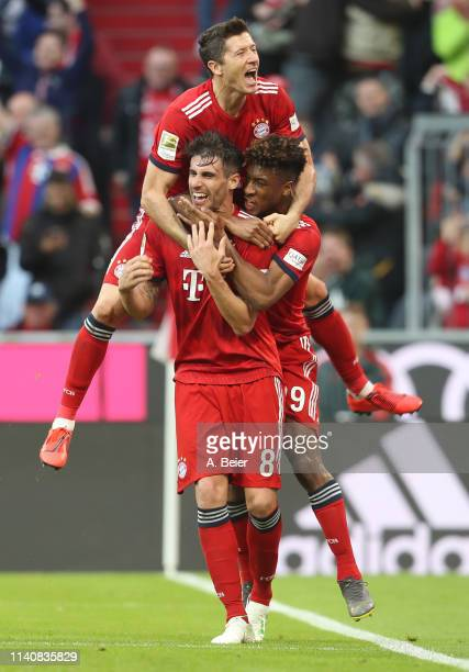 Javi Martinez of FC Bayern Muenchen celebrates his first goal with teammates Robert Lewandowski and Kingsley Coman during the Bundesliga match...