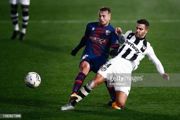 Javi Ontiveros of SD Huesca competes for the ball with Jose Campana of Levante UD during the La Liga Santander match between SD Huesca and Levante UD...