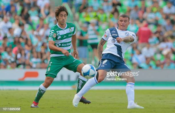 Javier Abella of Santos struggles for the ball with Christian Tabo of Puebla during the third round match between Santos Laguna and Puebla as part of...
