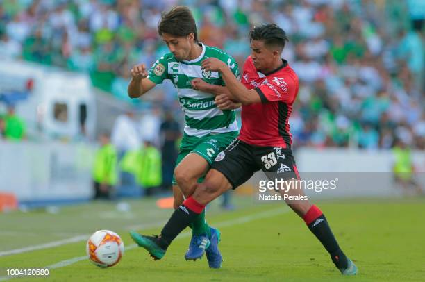 Javier Abella of Santos struggles the ball with Michael Chirino of Lobos during the 1st round match between Santos Laguna and Lobos BUAP as part of...