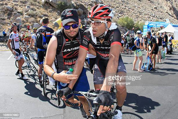 Javier Acevedo of Columbia riding for Jamis-Hagens Berman is escorted away from the finish by his soigneur after he won Stage Two of the 2013 Amgen...