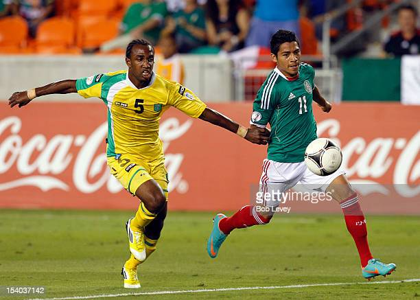 Javier Aquino fights off Walter Moore of Guyana in the first half at BBVA Compass Stadium on October 12 2012 in Houston Texas