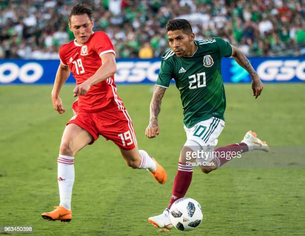 Javier Aquino of Mexico and Connor Roberts of Wales during the international friendly match between Mexico and Wales at the Rose Bowl on May 28 2018...