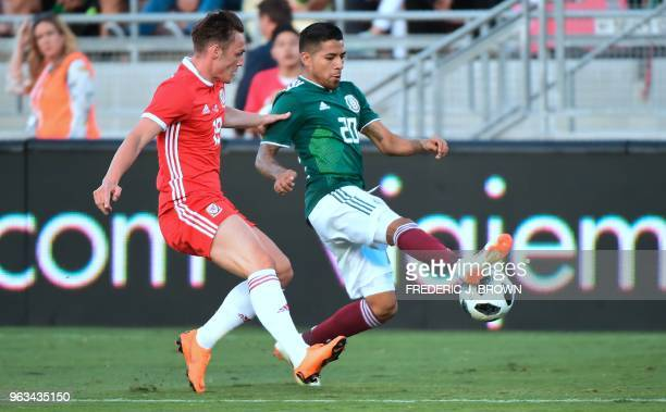 Javier Aquino of Mexico vies for the ball with Connor Roberts of Wales during their international soccer friendly at the Rose Bowl in Pasadena...