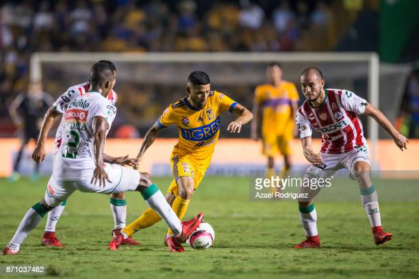 Javier Aquino of Tigres fights for the ball with Brayan Beckeles and Carlos Gonzalez of Necaxa during the 16th round match between Tigres UANL and...