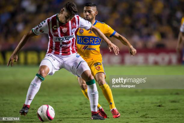 Javier Aquino of Tigres fights for the ball with Igor Lichnovsky of Necaxa during the 16th round match between Tigres UANL and Necaxa as part of the...