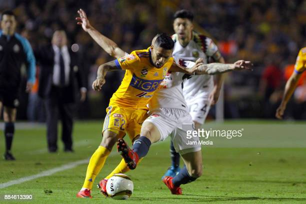 Javier Aquino of Tigres fights for the ball with Mateus Uribe of America during the semifinal second leg match between Tigres UANL and America as...