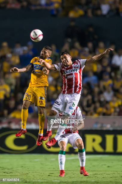 Javier Aquino of Tigres heads the ball with Luis Perez of Necaxa during the 16th round match between Tigres UANL and Necaxa as part of the Torneo...