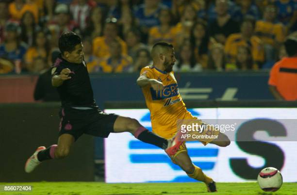 Javier Aquino of Tigres is marked by Jesus Sanchez of Chivas during their Mexican Apertura football tournament match at the Universitario stadium in...