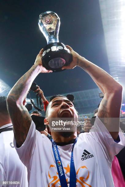 Javier Aquino of Tigres lifts the trophy to celebrate after winning the second leg of the Torneo Apertura 2017 Liga MX final between Monterrey and...