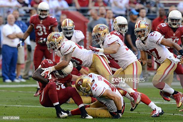 Javier Arenas of the Arizona Cardinals gets tackled by Darryl Morris of the San Francisco 49ers during a game at University of Phoenix Stadium on...