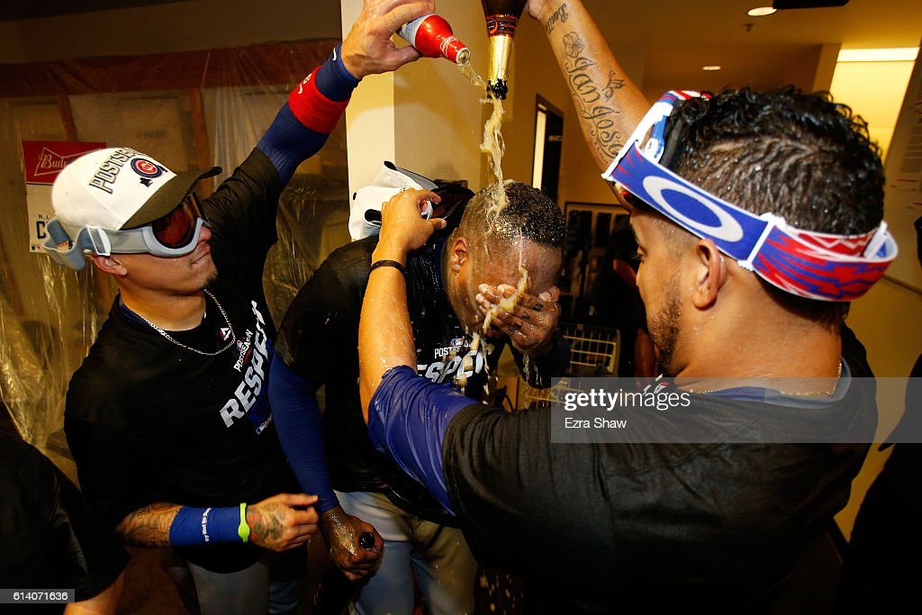 Javier Baez #9 (L) and Aroldis Chapman #54 (C) of the Chicago Cubs celebrate in the locker room after defeating the San Francisco Giants 6-5 in Game Four of their National League Division Series to advance to the National League Championship Series at AT&T Park on October 11, 2016 in San Francisco, California.