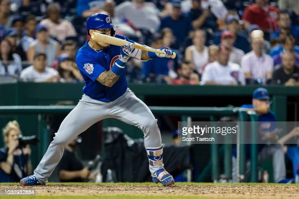 Javier Baez of the Chicago Cubs bunts in the game winning run against the Washington Nationals during the tenth inning at Nationals Park on September...
