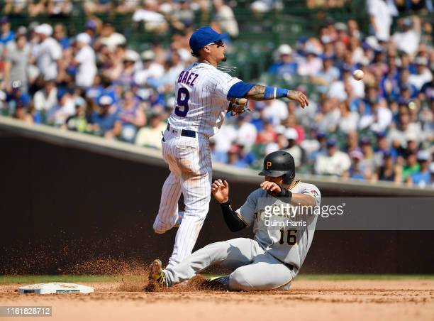 Javier Baez of the Chicago Cubs can't turn the double play against Jung Ho Kang of the Pittsburgh Pirates at Wrigley Field on July 13 2019 in Chicago...