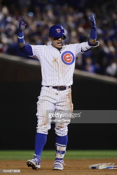 Javier Baez of the Chicago Cubs celebrates after hitting a RBI double in the eighth inning against the Colorado Rockies to score Terrance Gore during...