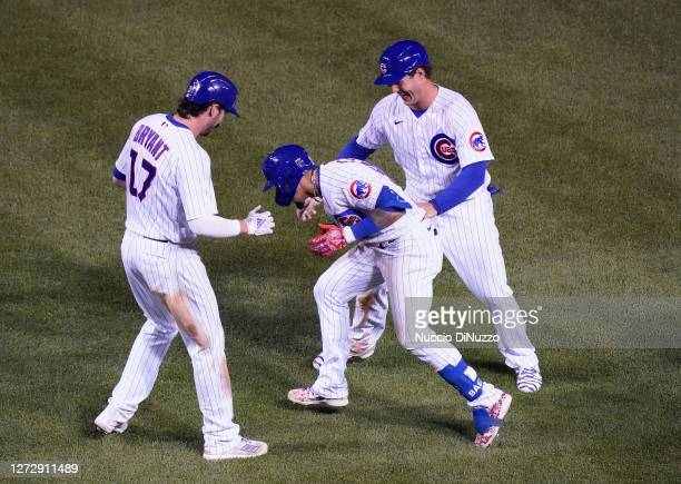 Javier Baez of the Chicago Cubs celebrates with Anthony Rizzo and Kris Bryant following his RBI during the tenth inning of a game against the...