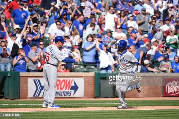 Javier Baez of the Chicago Cubs celebrates with thirdbase coach Brian Butterfield after hitting a home run in the fourth inning during the game...