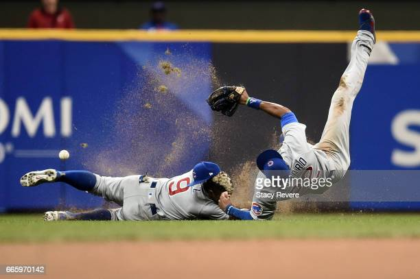 Javier Baez of the Chicago Cubs collides with Jason Heyward while chasing a fly ball during the sixth inning of a game against the Milwaukee Brewers...