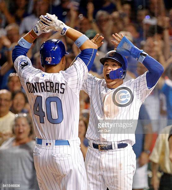 Javier Baez of the Chicago Cubs congratulates Willson Contreras after he hit a two run home run on the first pitch of his MLB debut against the...