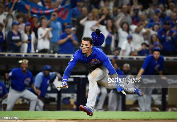 Javier Baez of the Chicago Cubs dives as he scores during the tenth inning of a baseball game against the San Diego Padres at PETCO Park on July 13...