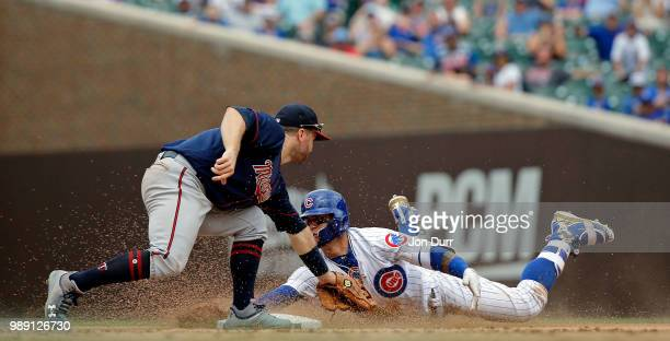 Javier Baez of the Chicago Cubs evades the tag of Brian Dozier of the Minnesota Twins for a double against the Minnesota Twins at Wrigley Field on...