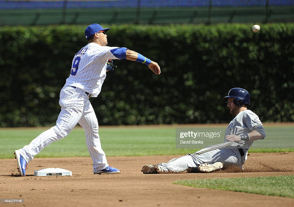 Javier Baez #9 of the Chicago Cubs forces out Jonathan Lucroy #20 of the Milwaukee Brewers during the first inning on September 1, 2014 at Wrigley Field in Chicago, Illinois.