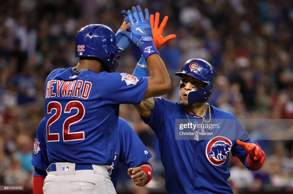 Javier Baez #9 of the Chicago Cubs high fives Jason Heyward #22 after hitting a three run home run against the Arizona Diamondbacks during the eighth inning of the MLB game at Chase Field on August 13, 2017 in Phoenix, Arizona.